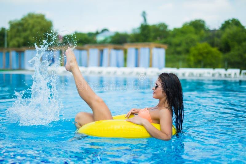 La mujer hermosa joven es relajante en piscina con el anillo de goma fotografía de archivo