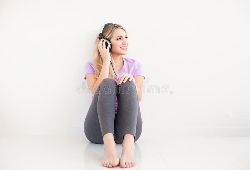 La mujer hermosa joven escucha música con los auriculares imagen de archivo libre de regalías