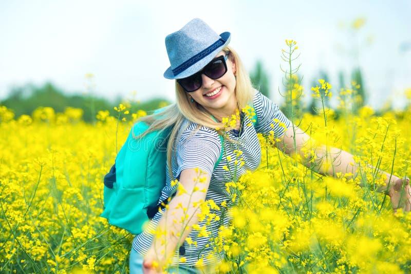 La mujer hermosa joven está caminando a lo largo de un campo floreciente en un día soleado fotografía de archivo