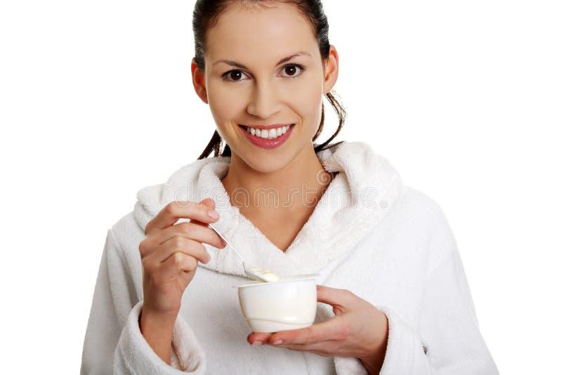 La mujer hermosa joven está comiendo el yogur. imágenes de archivo libres de regalías