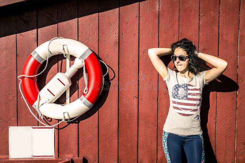La mujer hermosa joven está defendiendo cerca la pared de la casa roja fotos de archivo