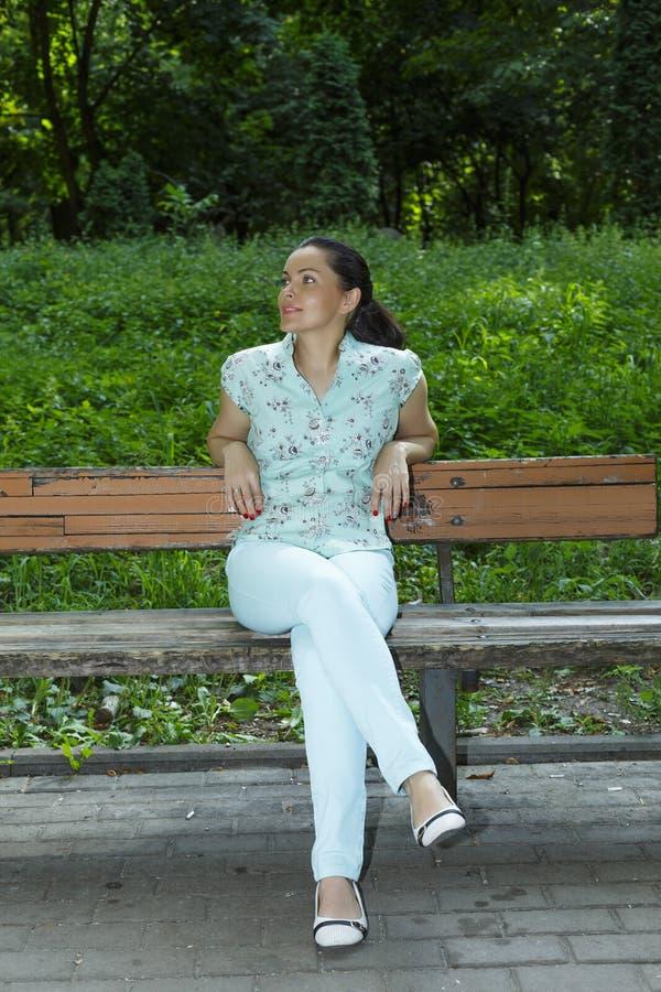 La mujer hermosa joven está descansando sobre un banco de parque Adultos jovenes imagenes de archivo