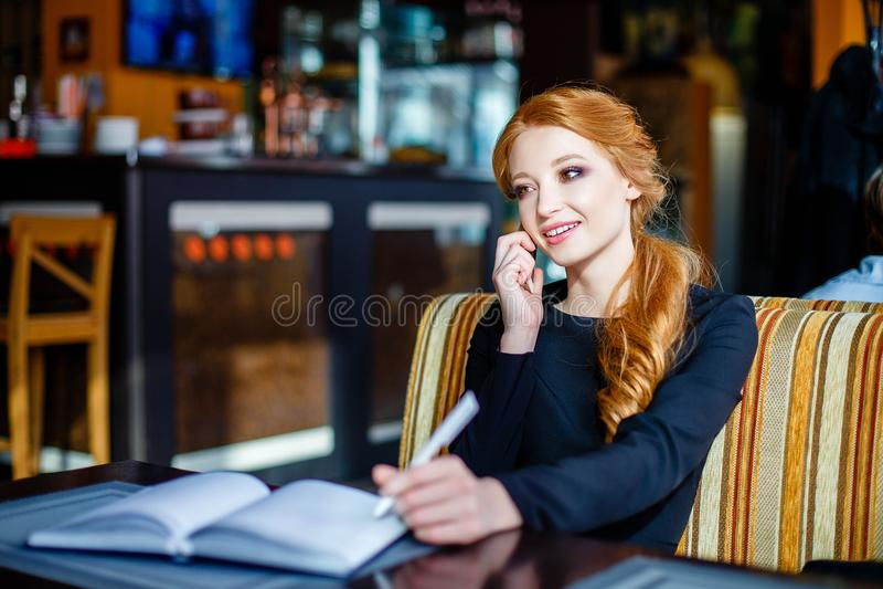 La mujer hermosa joven está hablando en el teléfono mientras que se sienta en un restaurante y hace notas en su cuaderno fotos de archivo libres de regalías