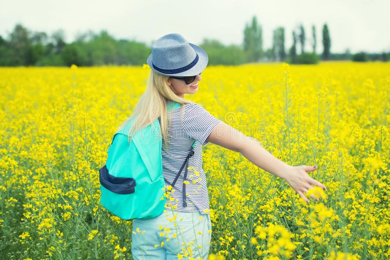 La mujer hermosa joven est? caminando a lo largo de un campo floreciente en un d?a soleado imagen de archivo