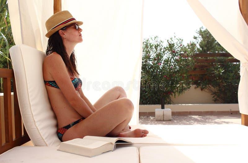La mujer hermosa joven lee un libro y se relaja sobre una cama de la piscina cerca del mar, Formentera, España imagen de archivo