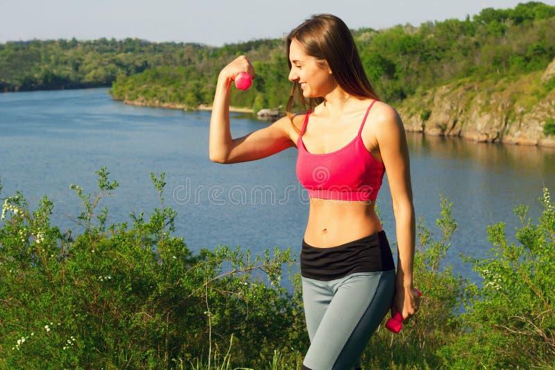 La mujer hermosa joven que hace deporte ejercita con dos pesas de gimnasia o imágenes de archivo libres de regalías