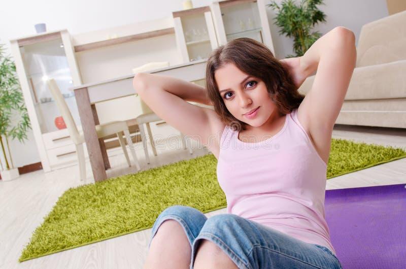 La mujer hermosa joven que hace ejercicios en casa fotografía de archivo
