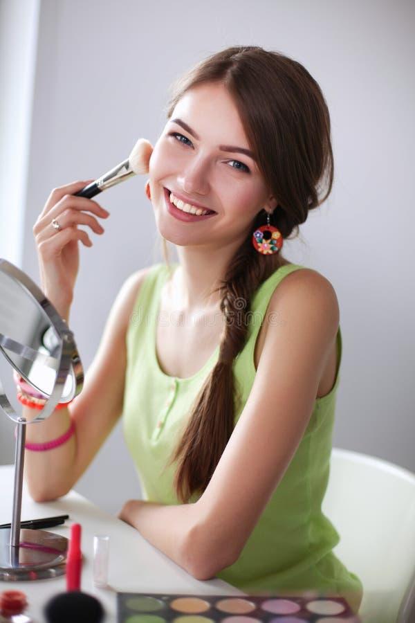 La mujer hermosa joven que hace maquillaje cerca duplica, sentándose en el escritorio imagenes de archivo