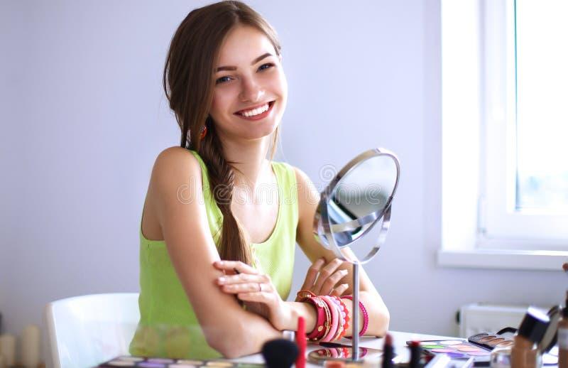 La mujer hermosa joven que hace maquillaje cerca duplica, sentándose en el escritorio imagen de archivo