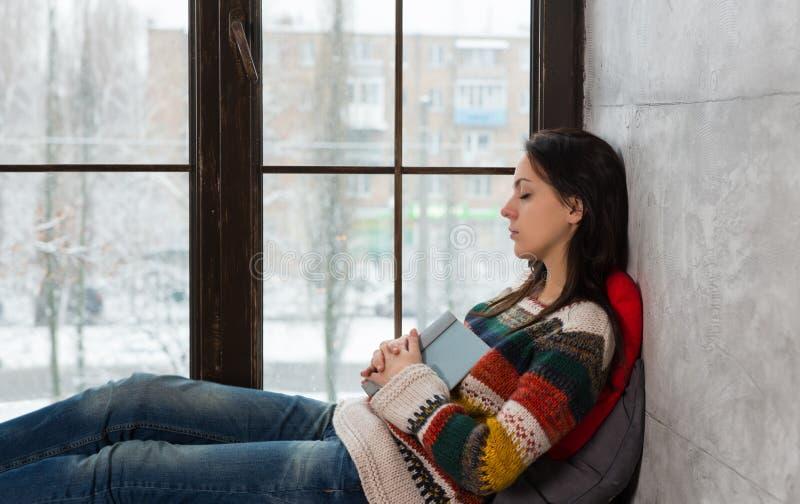 La mujer hermosa joven se cae dormido en el alféizar mientras que readin foto de archivo