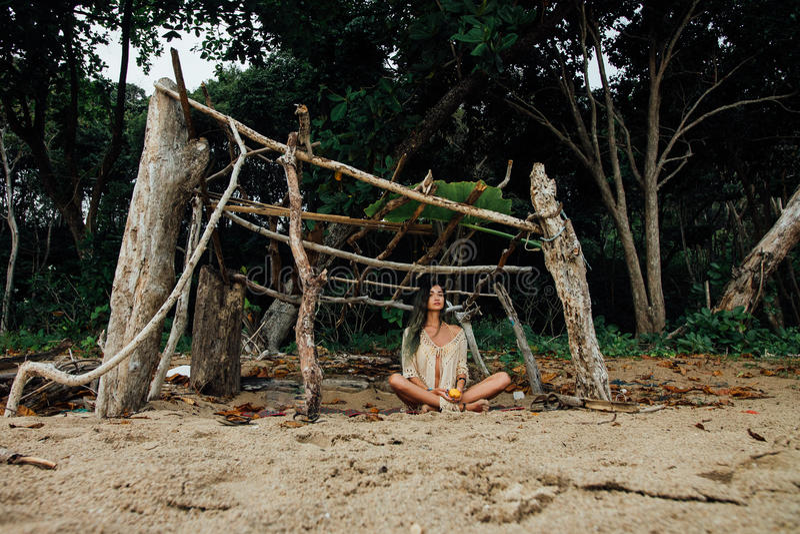 La mujer hermosa joven se sienta en la posición de loto encendido respecto a bosque tropical del fondo foto de archivo libre de regalías