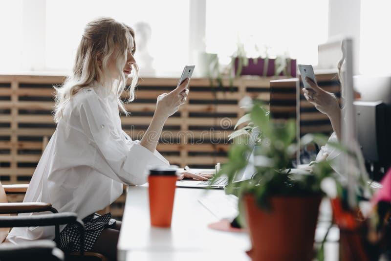 La mujer hermosa joven vestida en la camisa blanca está trabajando con el teléfono que se sienta en el escritorio con un ordenado imagenes de archivo