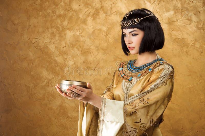 La mujer hermosa le gusta la reina egipcia Cleopatra con la taza en fondo de oro fotos de archivo libres de regalías