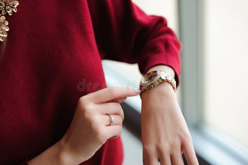 La mujer hermosa mira el reloj por la ventana fotografía de archivo libre de regalías