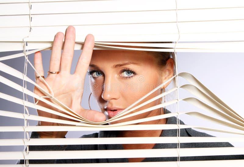 La mujer hermosa mira a través de persiana imagen de archivo libre de regalías