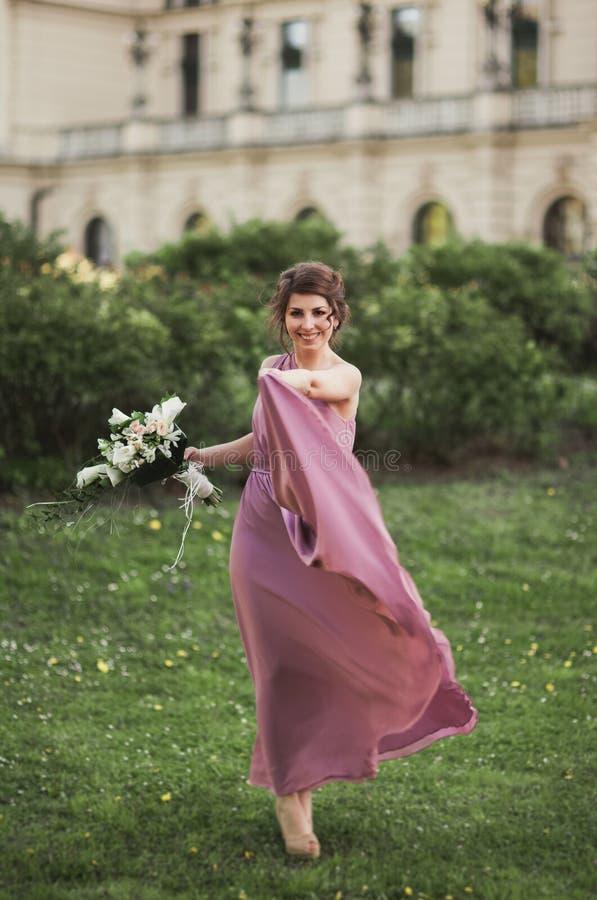 La mujer hermosa, novia en vestido rosado con el gran ramo fotografía de archivo libre de regalías