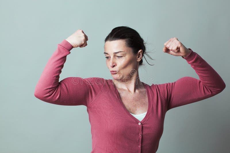 La mujer hermosa orgullosa 40s que la admira que dobla muscles fotos de archivo