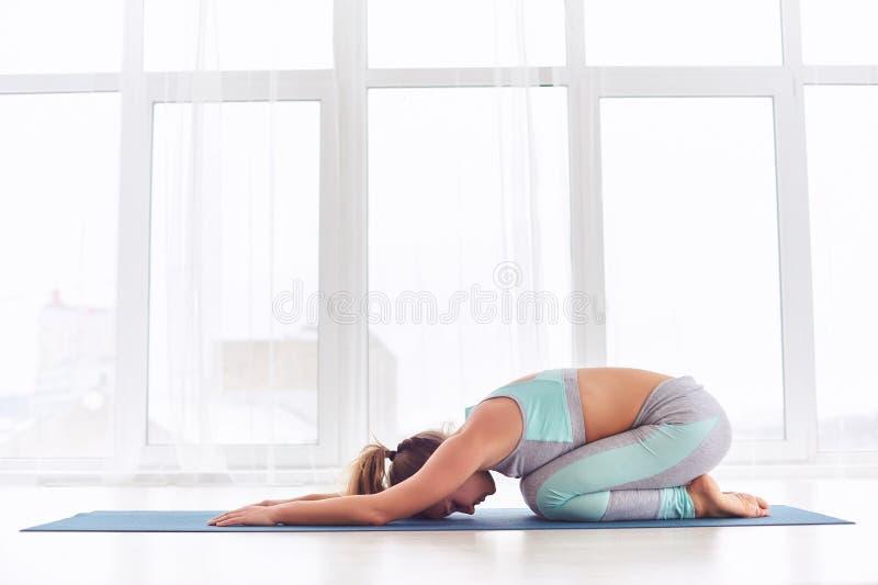La mujer hermosa practica el asana Balasana - actitud de la yoga del ` s del niño en el estudio de la yoga fotografía de archivo libre de regalías