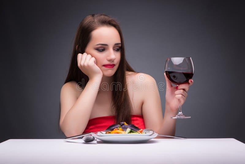 La mujer hermosa que come solamente con el vino imagen de archivo