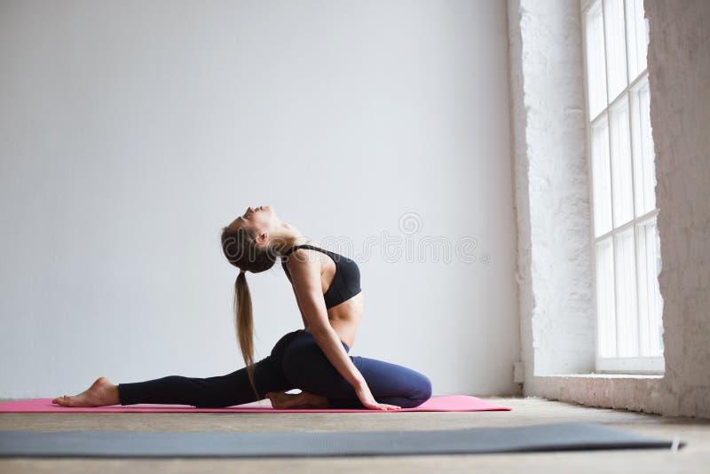 La mujer hermosa que hace estirar ejercita en el gimnasio foto de archivo