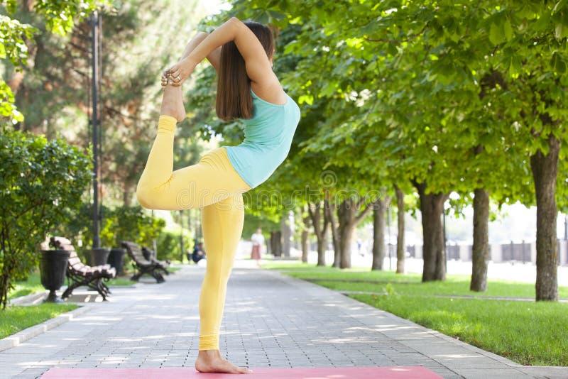 La mujer hermosa que hace yoga ejercita en el parque fotografía de archivo