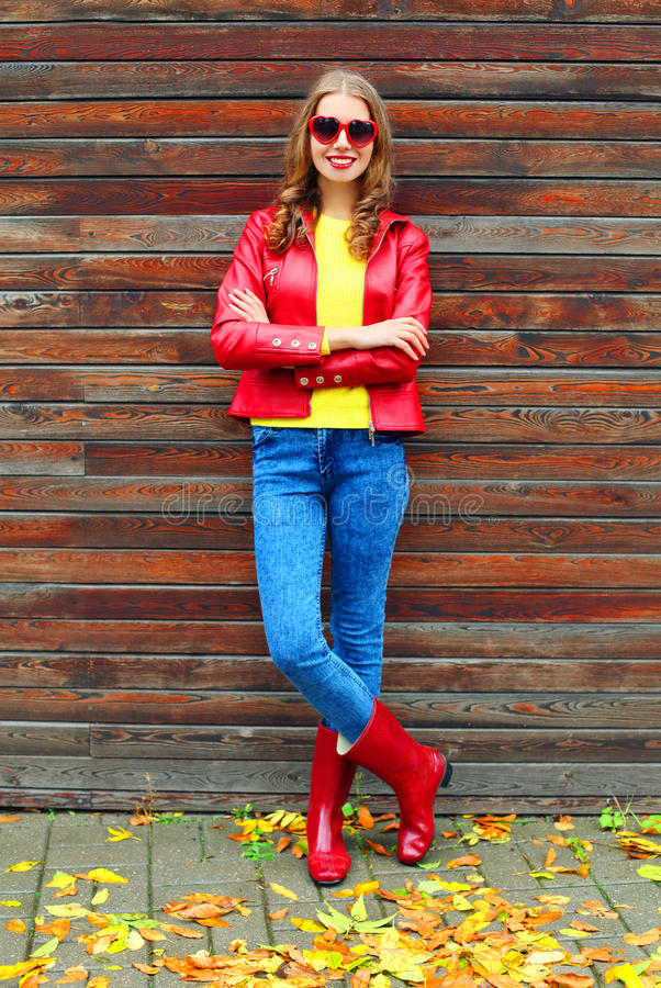 La mujer hermosa que lleva una chaqueta roja y las botas de goma en otoño diseñan cerca de las hojas amarillas fotografía de archivo libre de regalías