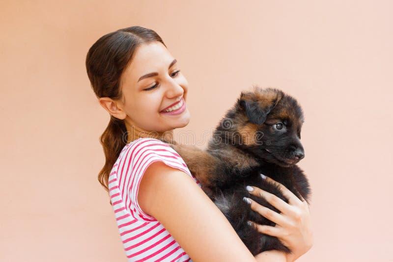 La mujer hermosa que se sostiene y que mira en el ` negro s del perrito observa foto de archivo libre de regalías