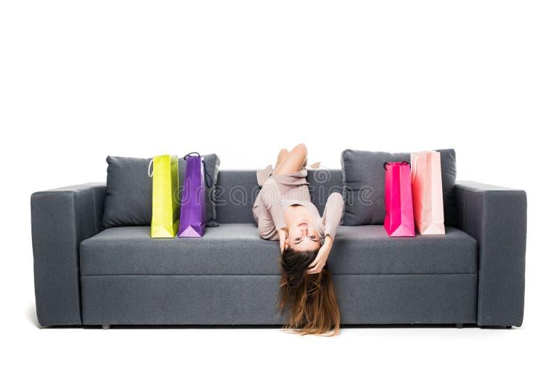 La mujer hermosa que sentaba en el sofá con muchos el panier alrededor de la actuación alegre y feliz con los brazos se separó de imagenes de archivo
