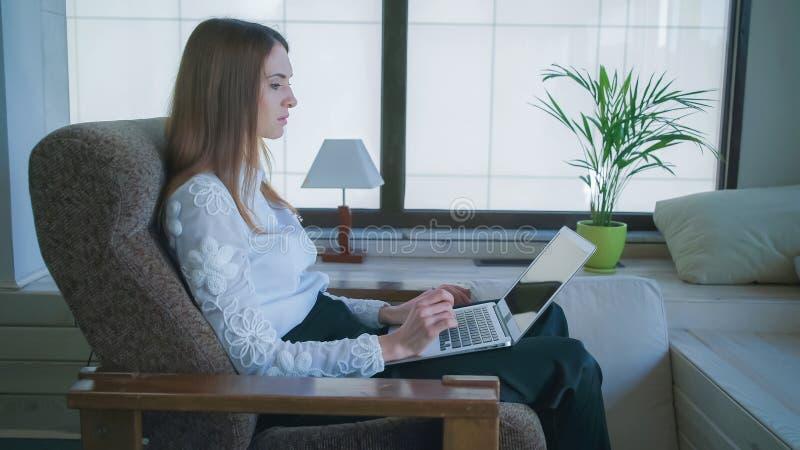 La mujer hermosa que trabaja en el ordenador portátil Cerca de Windows grande y de una flor en un pote imágenes de archivo libres de regalías