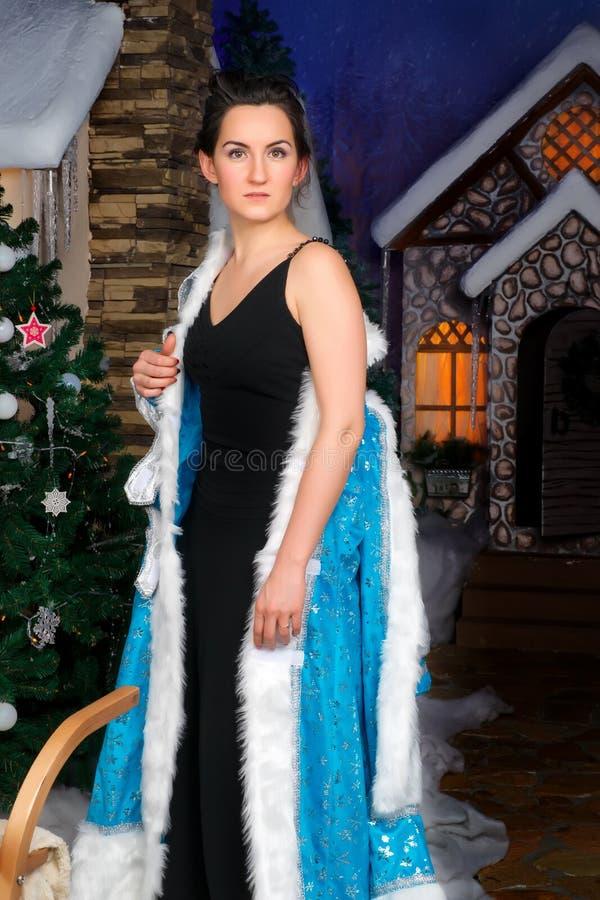 La mujer hermosa quita el vestido de lujo de la Navidad imagenes de archivo