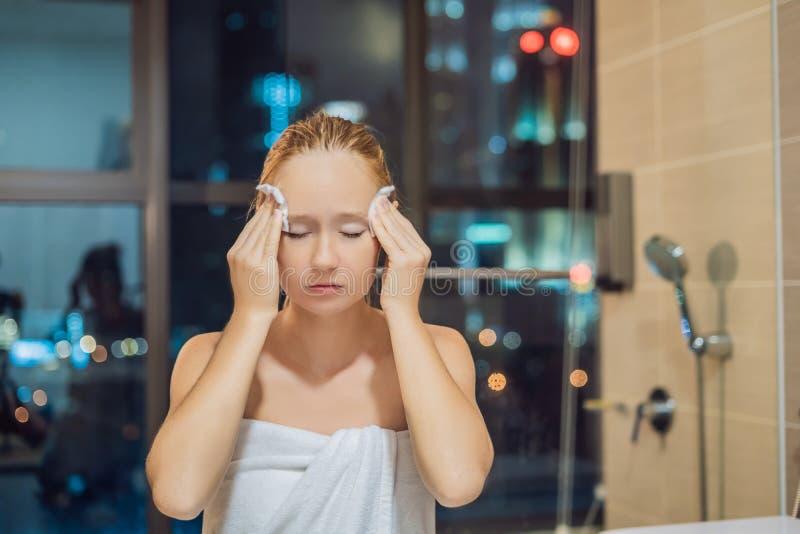 La mujer hermosa quita maquillaje en el fondo de un ingenio de la ventana imagen de archivo libre de regalías