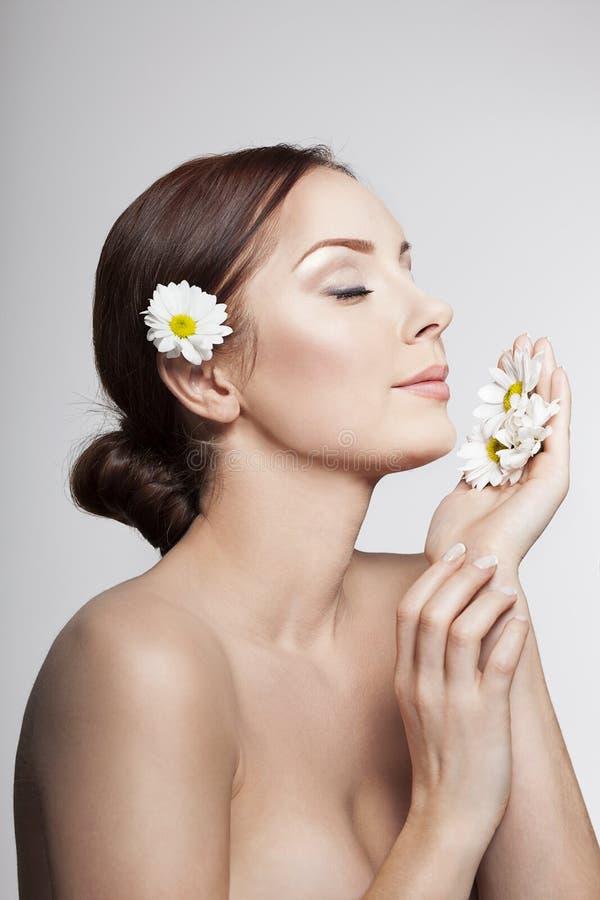 La mujer hermosa respira las flores de la manzanilla foto de archivo