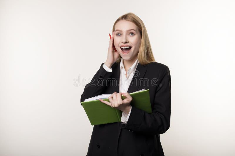 La mujer hermosa rubia feliz con los cuadernos verdes a disposición encontró una solución al probleme fotografía de archivo