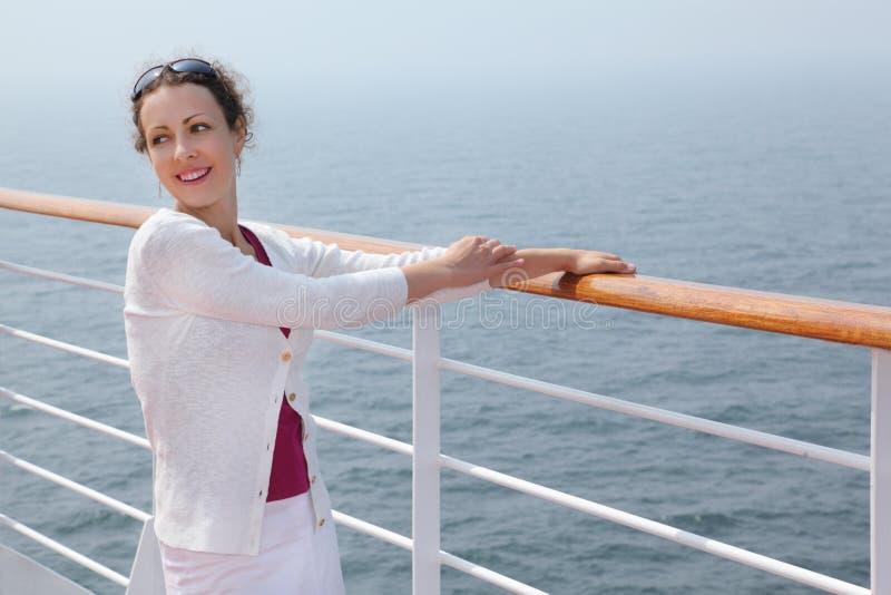 La mujer hermosa se coloca a bordo de la nave grande foto de archivo