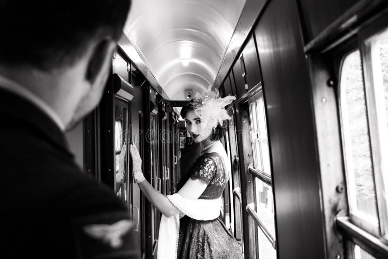 La mujer hermosa se vistió en vestido rojo del té del vintage del té en el tren locomotor fotos de archivo libres de regalías