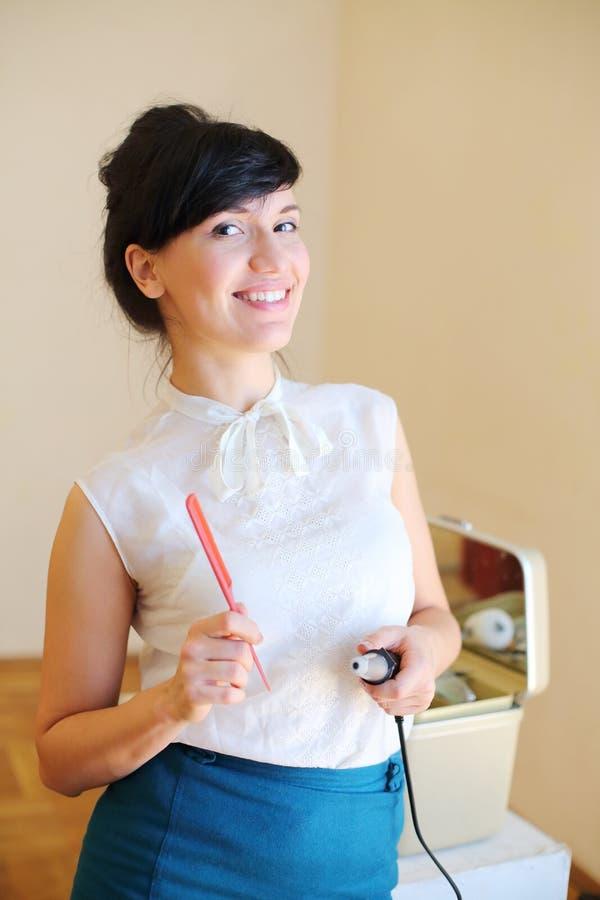 La mujer hermosa sostiene el peine rojo imagenes de archivo