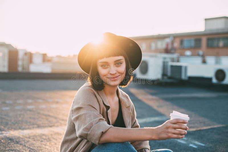 La mujer hermosa sostiene la taza de café en puesta del sol foto de archivo libre de regalías