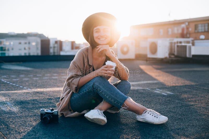 La mujer hermosa sostiene la taza de café en puesta del sol fotografía de archivo libre de regalías