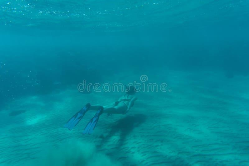 La mujer hermosa subacuática en bikini bucea sobre el arrecife de coral en el mar imagenes de archivo