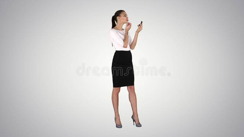 La mujer hermosa, te?e su rosa de la barra de labios de los labios, mirando en el espejo en fondo de la pendiente fotos de archivo libres de regalías