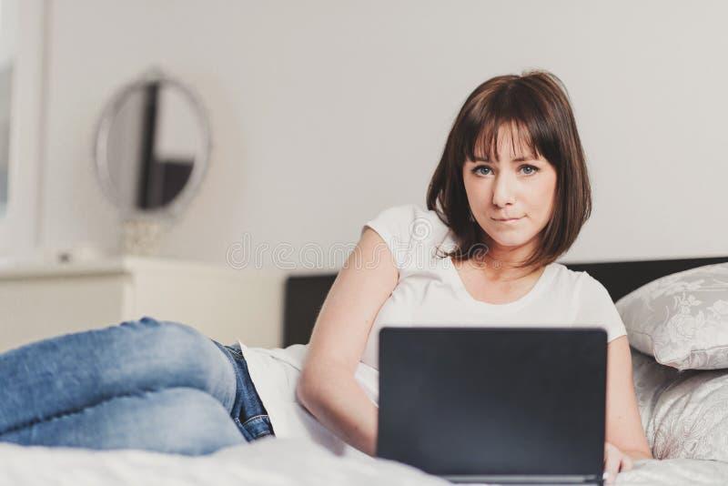 La mujer hermosa trabaja en el ordenador portátil en dormitorio imagen de archivo