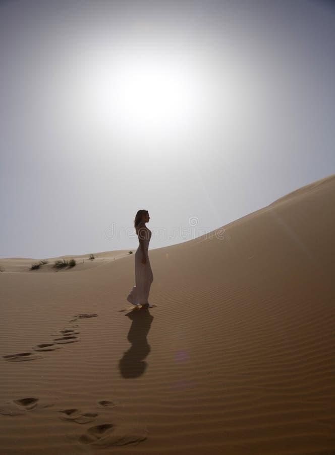 La mujer hermosa y delgada camina en el desierto imagenes de archivo