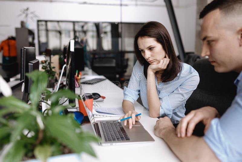 La mujer hermosa y el individuo vestidos en ropa del estilo de la oficina están trabajando así como el ordenador portátil que se  fotos de archivo libres de regalías