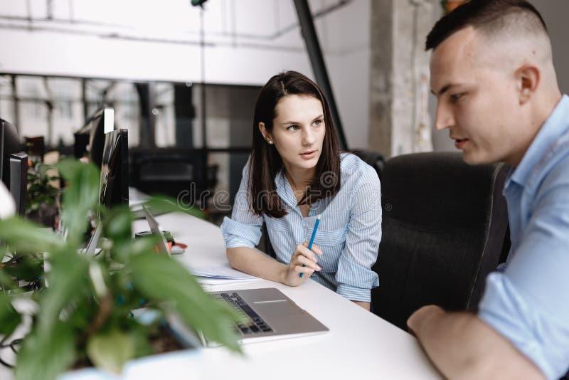 La mujer hermosa y el individuo vestidos en ropa del estilo de la oficina están trabajando así como el ordenador portátil que se  fotografía de archivo