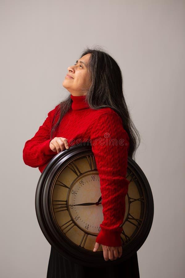 La mujer hisp?nica con el reloj debajo del brazo mira para arriba fotos de archivo libres de regalías