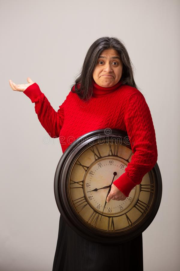 La mujer hisp?nica confundida sostiene el reloj debajo del brazo inconsciente de futuro imagenes de archivo