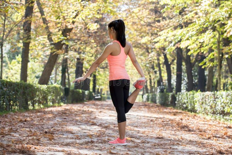 La mujer hispánica hermosa del deporte en la ropa de deportes que estira flexibilidad que hace feliz después sonriente del cuerpo imágenes de archivo libres de regalías