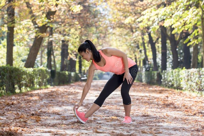 La mujer hispánica hermosa del deporte en la ropa de deportes que estira flexibilidad que hace feliz después sonriente del cuerpo imagenes de archivo