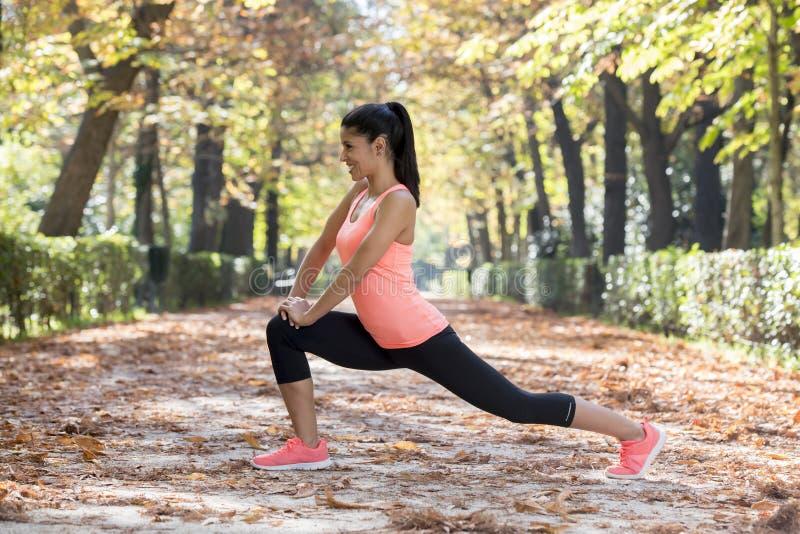 La mujer hispánica hermosa del deporte en la ropa de deportes que estira flexibilidad que hace feliz después sonriente del cuerpo fotos de archivo