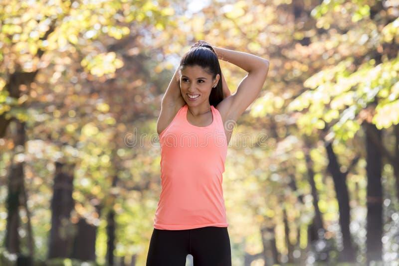 La mujer hispánica hermosa del deporte en la ropa de deportes que estira flexibilidad que hace feliz después sonriente del cuerpo fotografía de archivo
